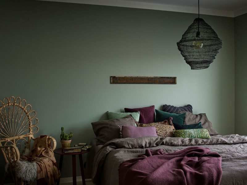 green colour accent wall in bedroom with bohemian style pillows and lamp